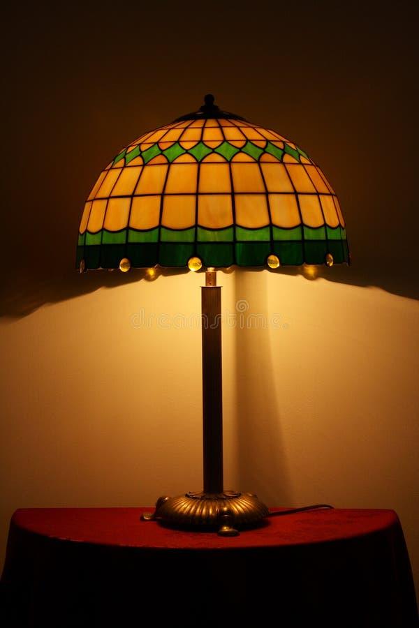 стеклянным таблица запятнанная светильником стоковые фото