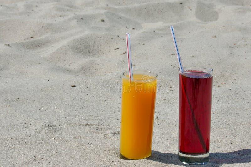 2 стеклянных стекла с соком манго и вишни с tubules Песчаный пляж на летний день стоковая фотография rf