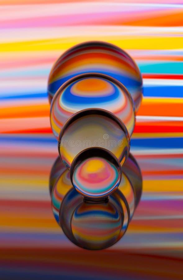 4 стеклянных хрустального шара в ряд с радугой красочной светлой картины за ими стоковое фото