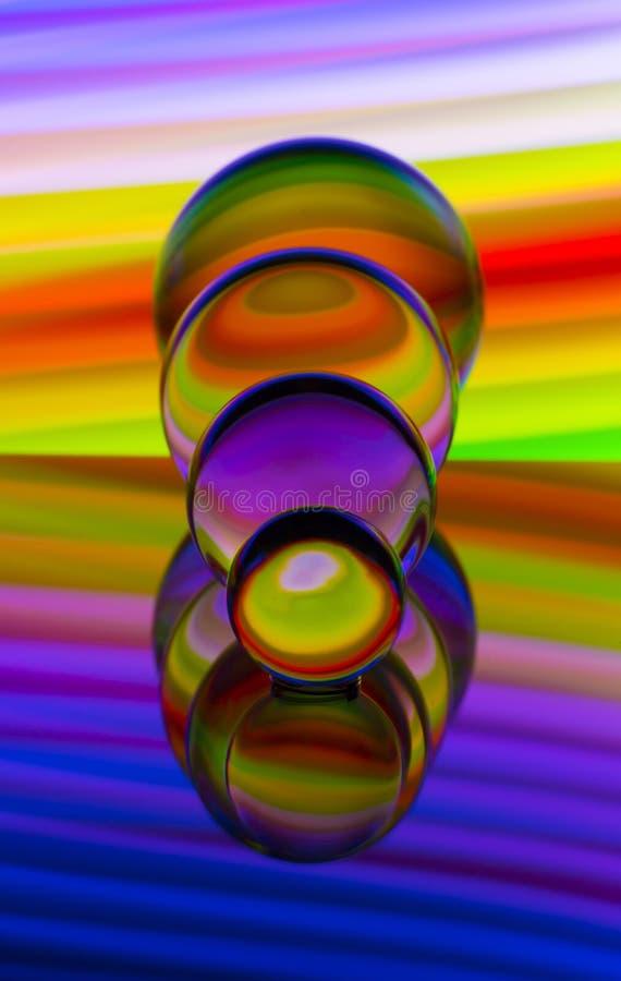 4 стеклянных хрустального шара в ряд с радугой красочной светлой картины за ими стоковые изображения