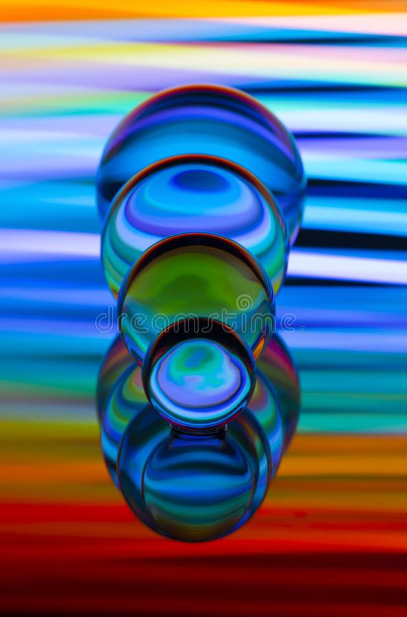 4 стеклянных хрустального шара в ряд с радугой красочной светлой картины за ими стоковое изображение