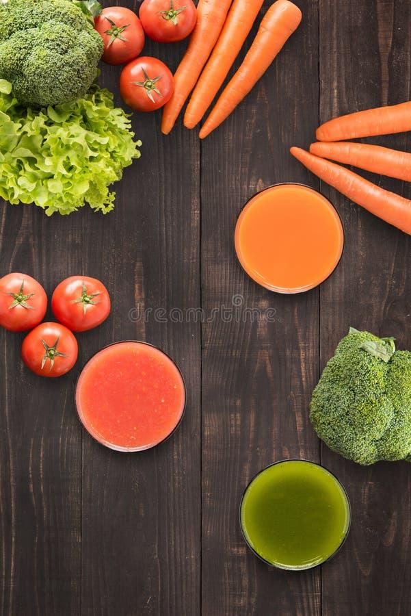 Стекла вкусных свежих vegetable соков на деревянной предпосылке стоковая фотография rf