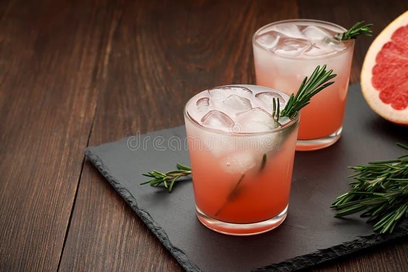 2 стекла лета цитруса выпивают с грейпфрутом и розмариновым маслом на темной предпосылке стоковое фото rf