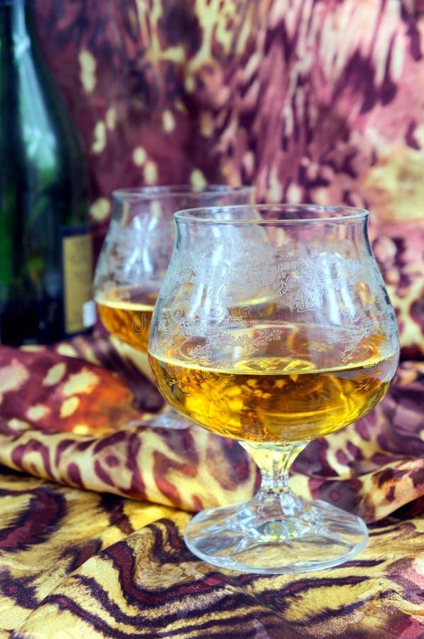 2 стекла коньяка с бутылкой на покрашенной предпосылке стоковое фото rf