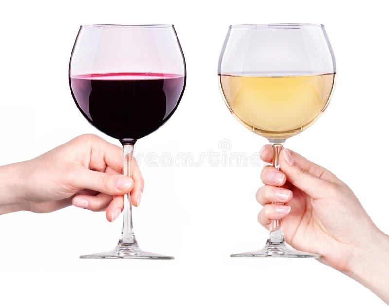 Стекла красного и белого вина в изолированной руке стоковое изображение