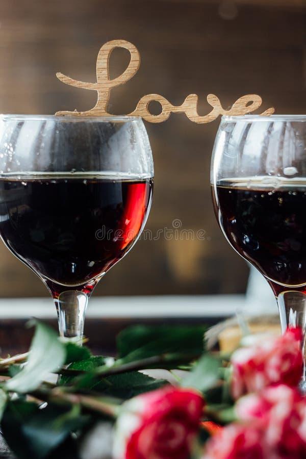 Стекла дня валентинки wine с письмами ЛЮБЯТ, цветки и сердца стоковые фотографии rf