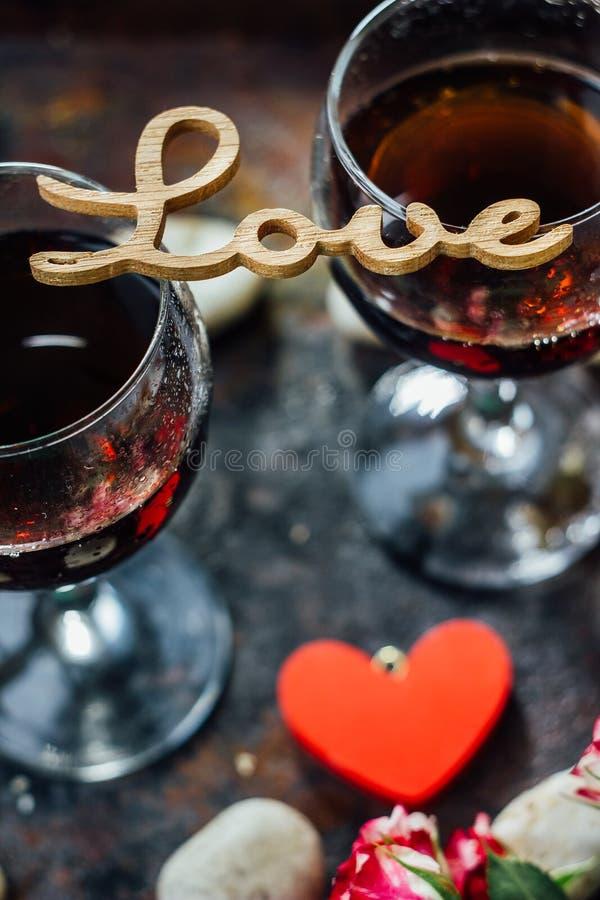 Стекла дня валентинки wine с письмами ЛЮБЯТ, цветки и сердца стоковая фотография rf