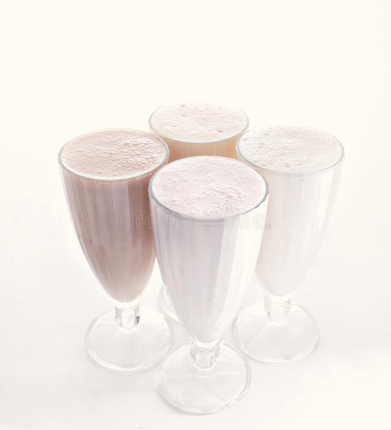 4 стекла различных milkshakes шоколада, клубники и ванили изолированных на белой предпосылке стоковые фото