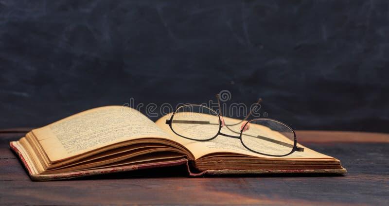 Стекла старой книги и глаза на предпосылке классн классного стоковая фотография rf