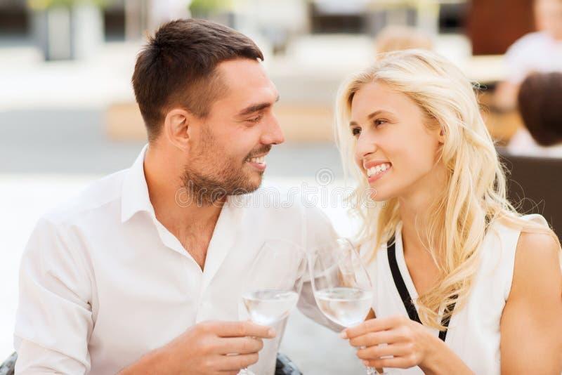 Стекла счастливых пар clinking на салоне ресторана стоковое изображение