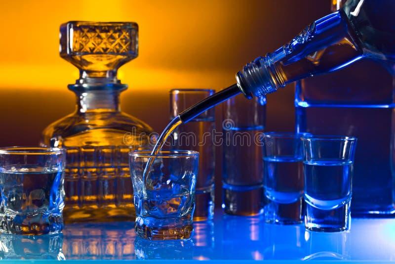 Стекла с алкогольными напитками на стеклянном столе в баре стоковое фото rf