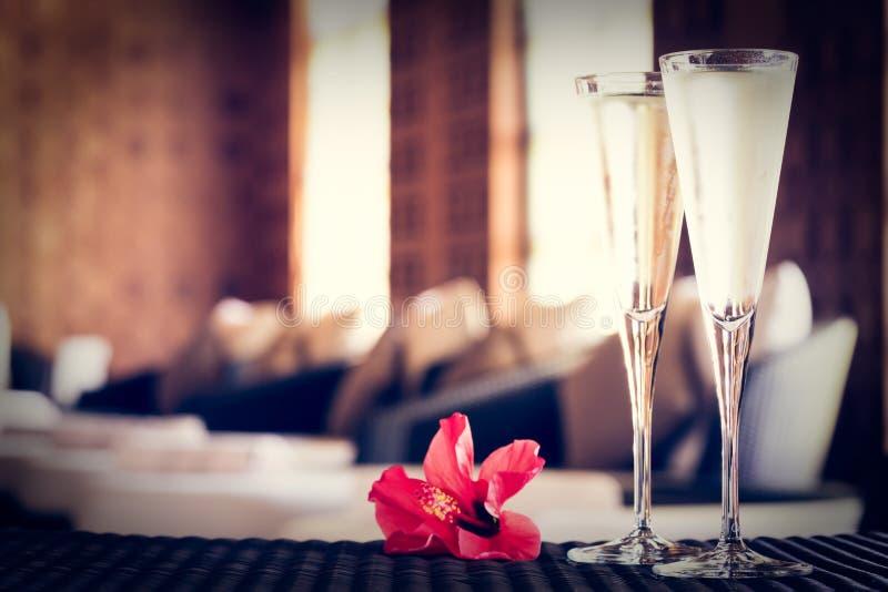 2 стекла шампанского с красным цветком в салоне курорта Ti курорта стоковое фото