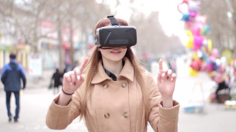 Стекла шлемофона виртуальной реальности vr маленькой девочки нося имея потеху играя снаружи в улице в бежевом пальто outwer видеоматериал