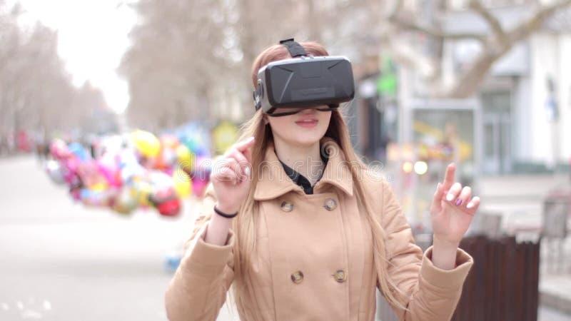 Стекла шлемофона виртуальной реальности vr счастливой девушки нося имея потеху играя снаружи в улице в бежевом пальто outwer сток-видео
