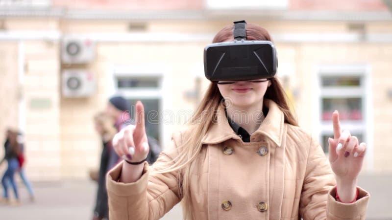Стекла шлемофона виртуальной реальности vr счастливой маленькой девочки нося имея потеху играя снаружи на улице в беже outwear па акции видеоматериалы