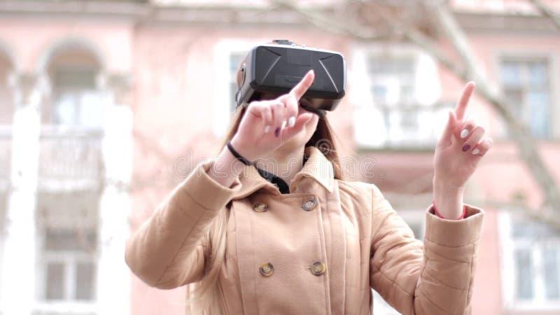 Стекла шлемофона vr виртуальной реальности виртуального пространства счастливой женщины нося в беже outwear пальто имея потеху сн сток-видео