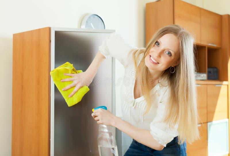 Стекло белокурой женщины очищая стоковая фотография rf