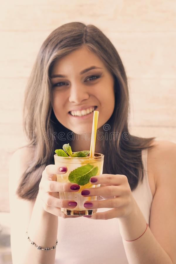 Стекло воды вытрезвителя с лимоном, льдом и свежей мятой в руках маленькой девочки стоковое фото rf