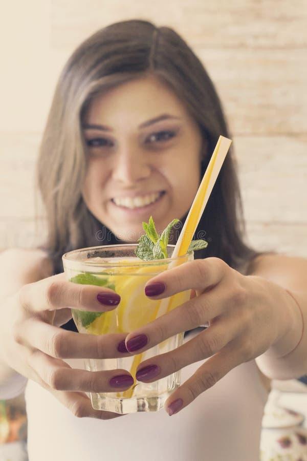 Стекло воды вытрезвителя с лимоном, льдом и свежей мятой в руках маленькой девочки стоковые фотографии rf