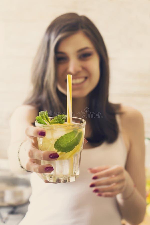Стекло воды вытрезвителя с лимоном, льдом и свежей мятой в руках маленькой девочки стоковое фото