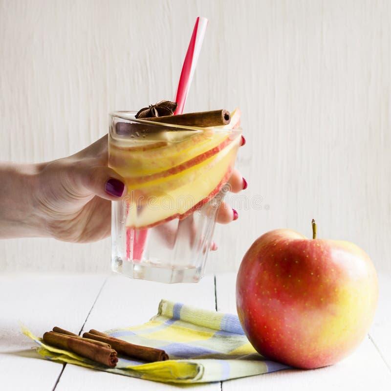 Стекло воды вытрезвителя с яблоком, циннамоном и анисовкой в руках маленькой девочки стоковая фотография
