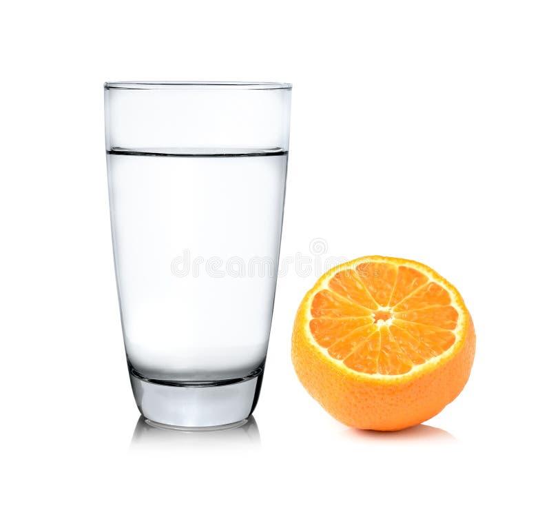 Стекло воды и половинного оранжевого плодоовощ на белой предпосылке стоковые фотографии rf