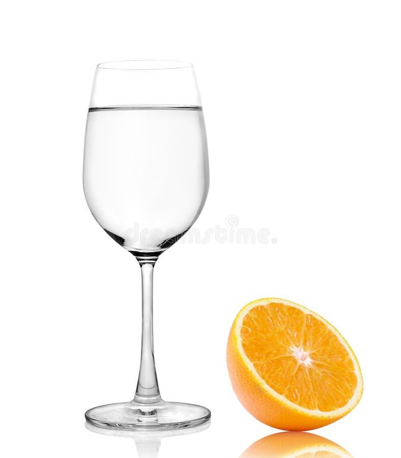 Стекло воды и половинного оранжевого плодоовощ на белой предпосылке, свежее стоковые изображения