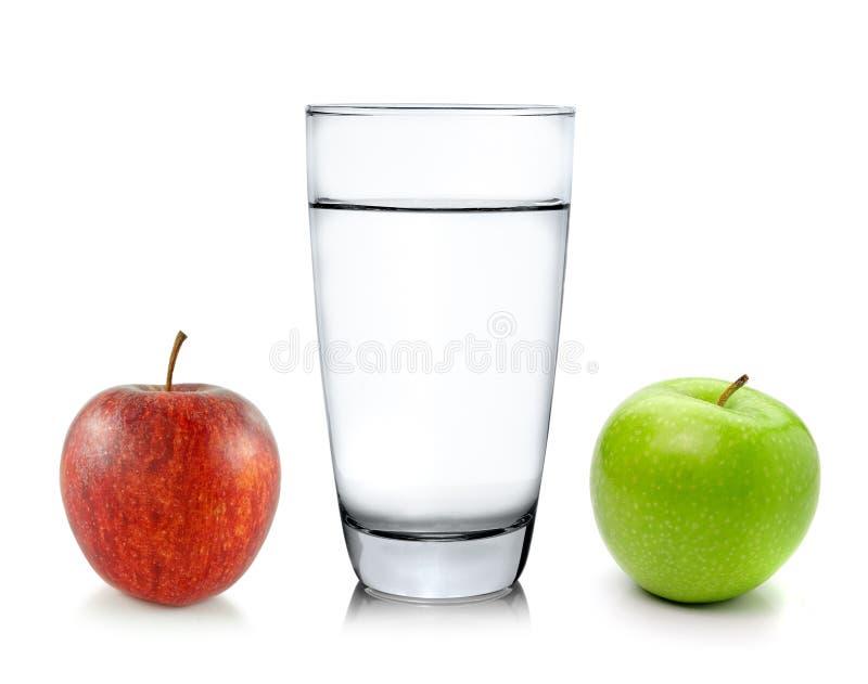 Стекло воды и яблока стоковые изображения