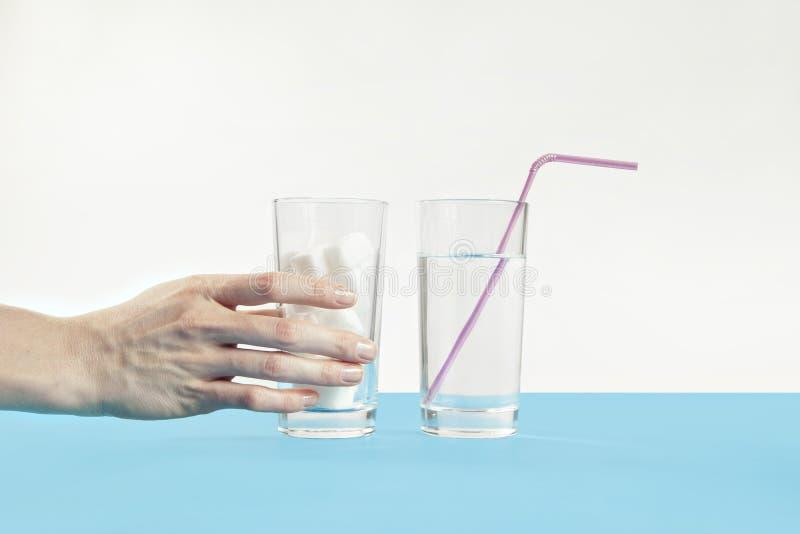 Стекло воды против сахара, заболевания диабета, сладостной наркомании стоковое фото