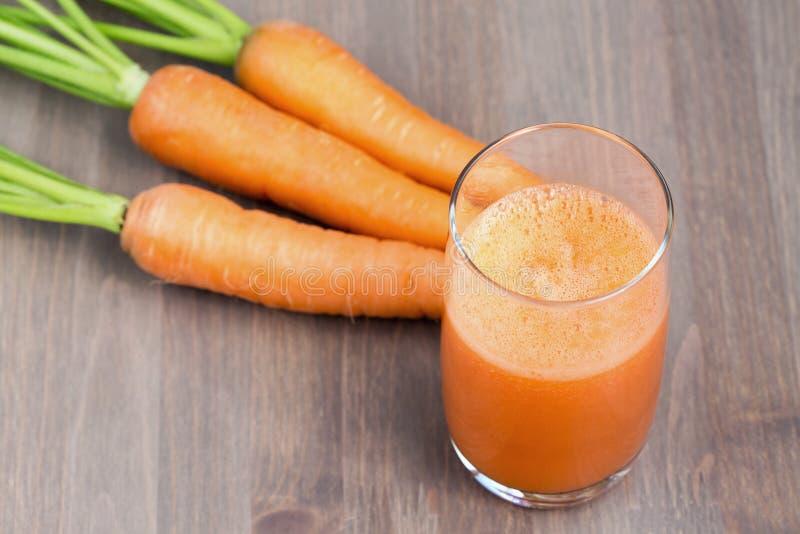 Стекло здорового smoothie моркови с морковами на деревянной предпосылке стоковые изображения rf