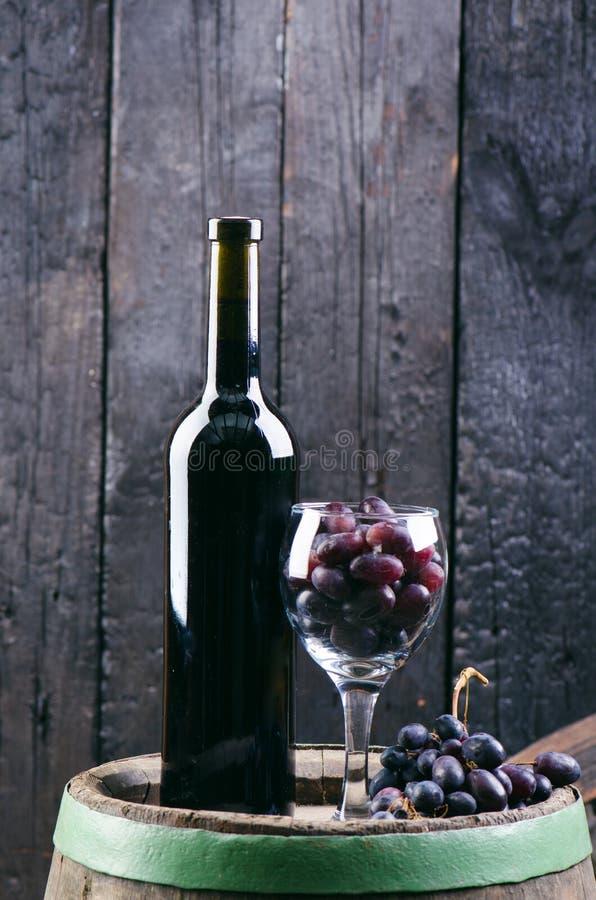 Стекло и бутылка вина на деревянном бочонке Сгорели, черные деревянная предпосылка Винтаж Copyspace для текста Виноградины и зеле стоковое изображение rf
