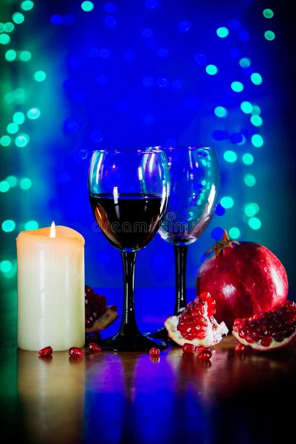 Стекло красного вина, зрелого гранатового дерева, и горя свечи на таблице стоковое изображение rf