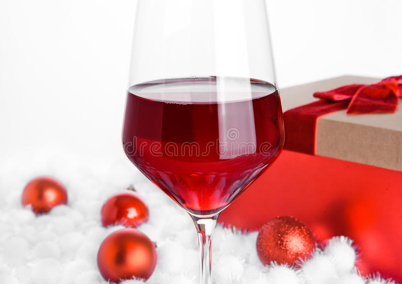 Стекло красного вина на снеге с шариками рождества стоковая фотография