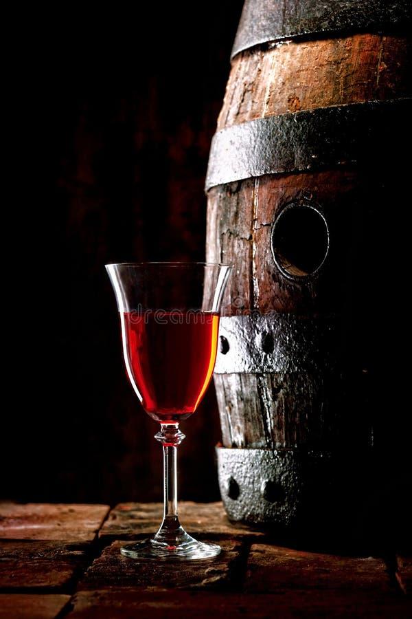 Стекло красного вина рядом с бочкой дуба стоковое изображение rf