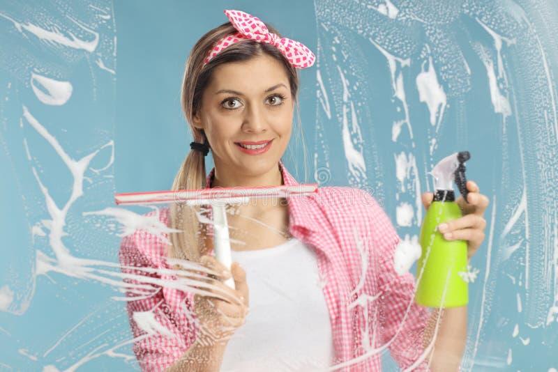 Стекло молодой женщины очищая с скребком и тензидом стоковая фотография rf
