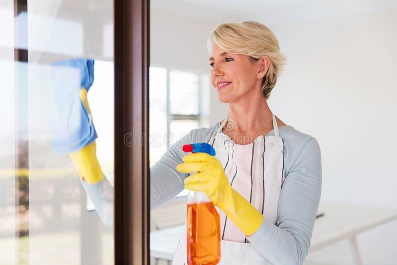 Стекло окна чистки женщины стоковая фотография rf