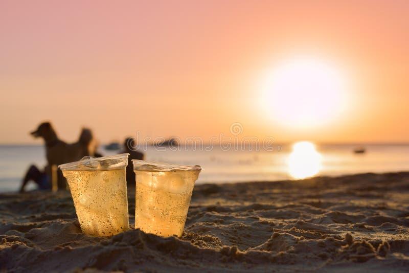 Стекло пива на песке пляжа на заходе солнца стоковое фото