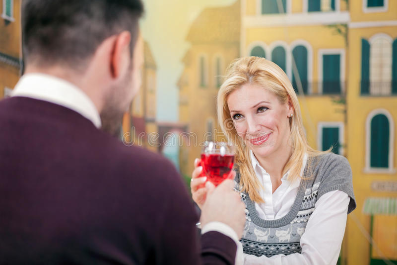Стекло питья даты молодых счастливых пар романтичное красного вина в покое стоковая фотография