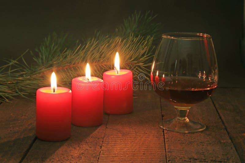 Стекло рябиновки или коньяка и свечи на деревянном столе Состав торжества стоковое фото rf