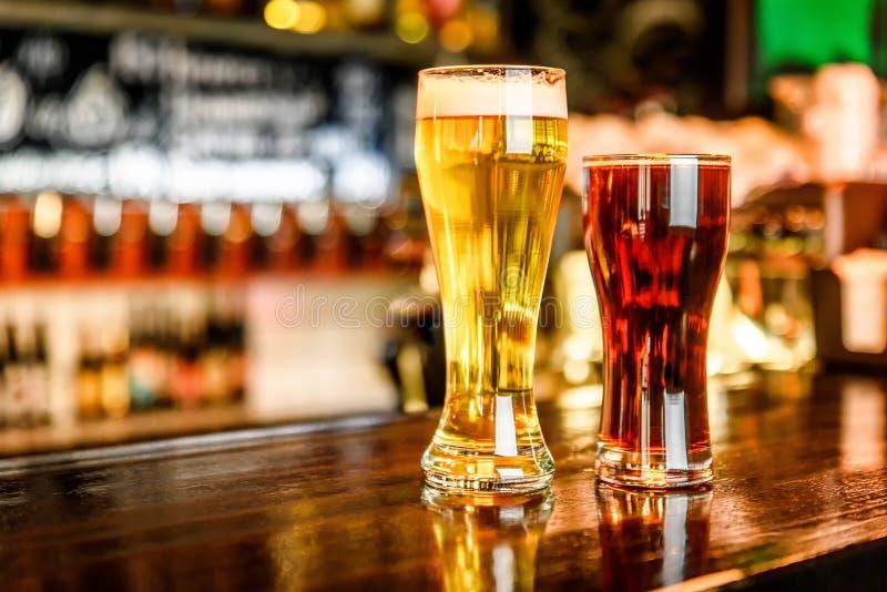 Стекло светлого и темного пива на пабе с предпосылкой bokeh стоковое фото
