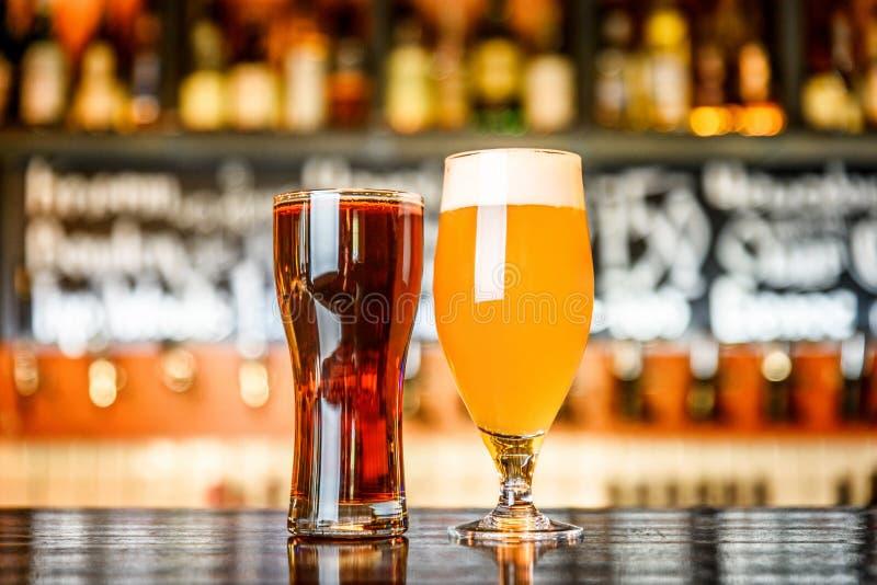 Стекло светлого и темного пива на пабе с предпосылкой bokeh стоковые фотографии rf