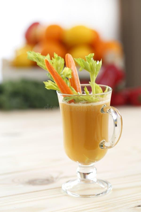 Стекло сока в latte стекла mugs с частями сельдерея и морковей с покрашенной предпосылкой стоковое фото