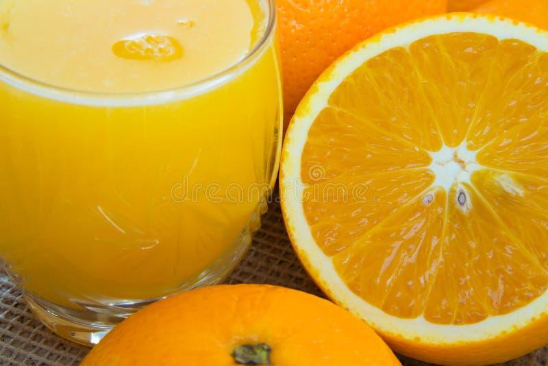 Стекло сока и конца-вверх апельсинов стоковые изображения rf
