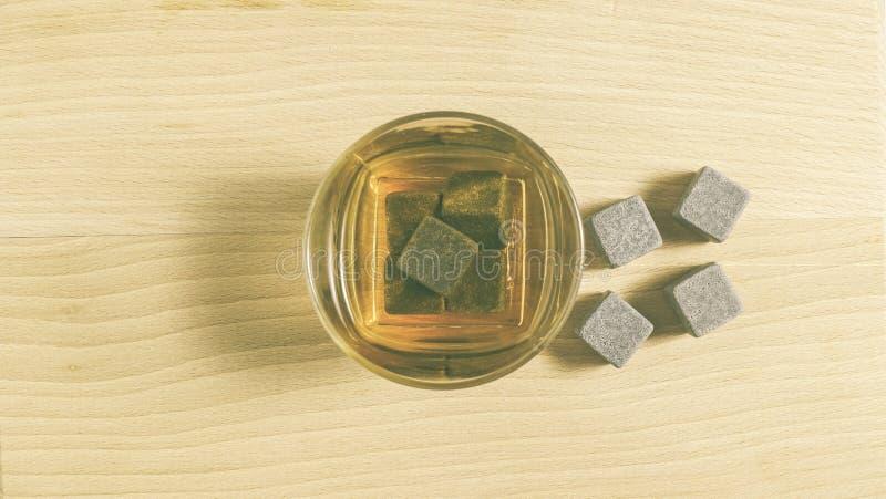 Стекло с камнями вискиа и льда на деревянном столе стоковое фото