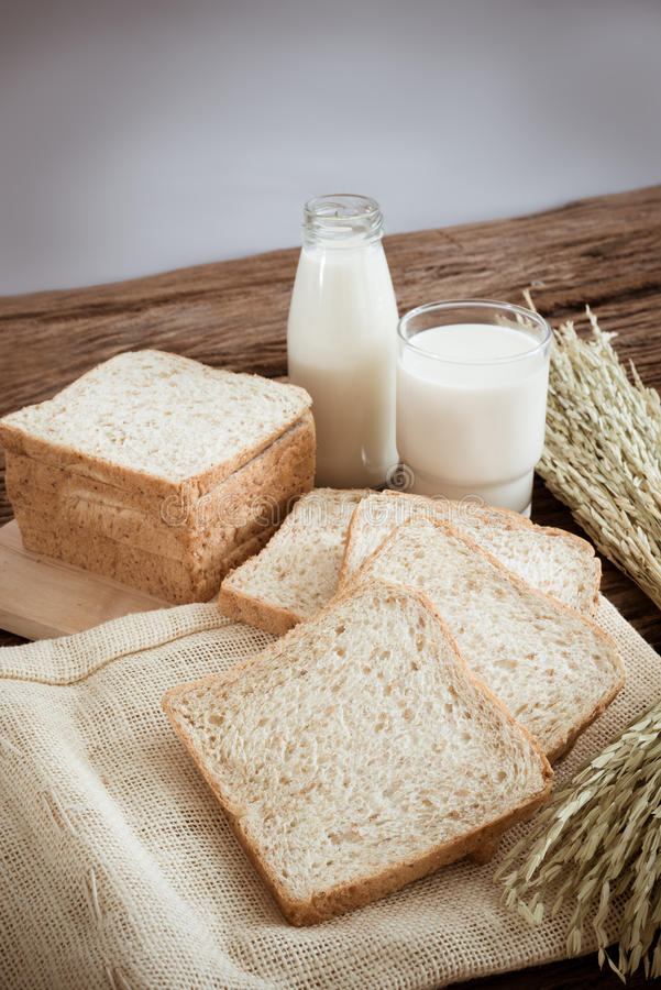 Стекло хлеба молока и всей пшеницы на деревянной доске стоковая фотография rf