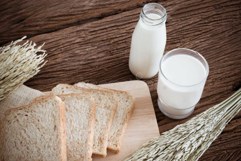 Стекло хлеба молока и всей пшеницы на деревянной доске стоковое фото rf