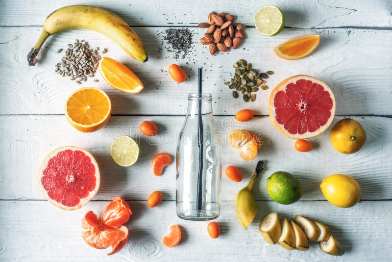Стеклянная бутылка окруженная различными плодоовощами и гайками на белом взгляд сверху деревянного стола стоковые фото