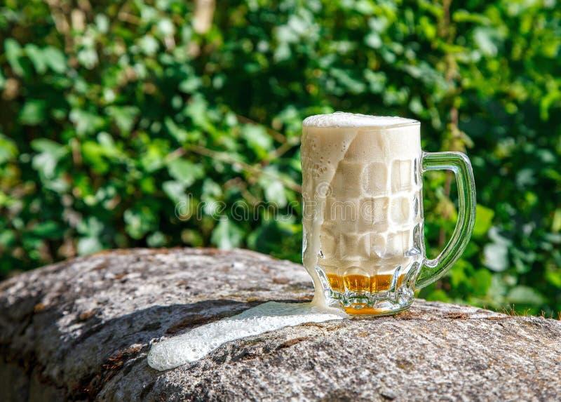 Стеклянная кружка при пиво стоя на большом камне стоковые фото