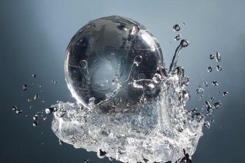 Стеклянная планета глобуса в выплеске воды падения на голубой предпосылке иллюстрация штока