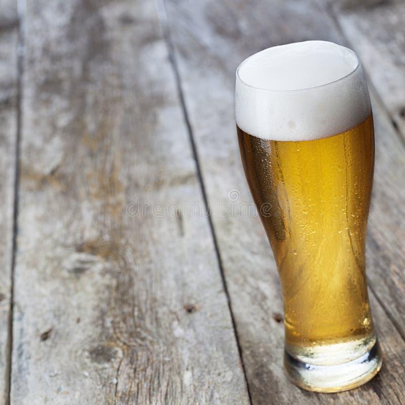 Стеклянное пиво на деревянной предпосылке стоковое изображение